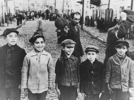 Jewish children in the Lublin ghetto. The men behind them were forced to remove their caps in deference to a German officer standing next to the photographer. Poland, 1941–1942