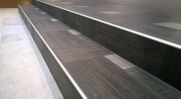 Peldaños de gradas/ escaleras con perfiles curvos de acero en los bordes. Diseño y creatividad en la arquitectura interior.