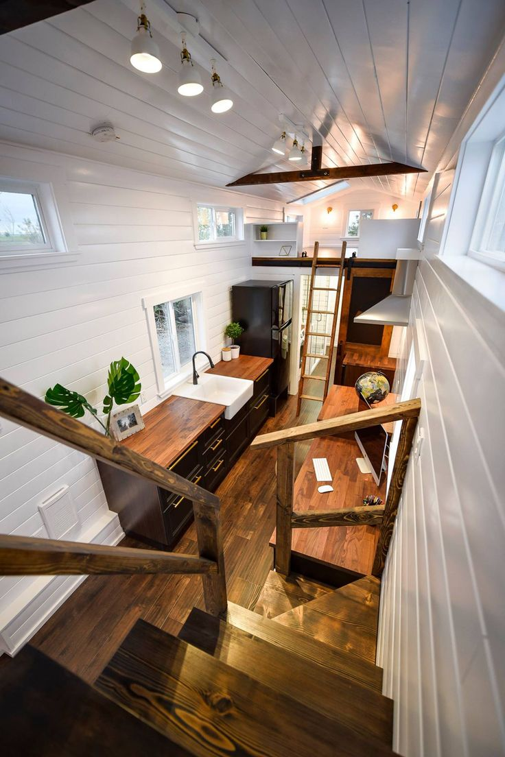 The custom tiny house has glossy white walls with dark flooring and trim. Exposed beams and gold wall sconces add a classy finish to the living room.