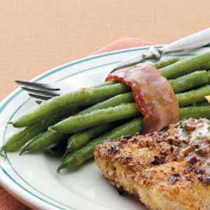 """Bacon-Wrapped Green Beans Recipe -Fresh green beans are wrapped in bacon and covered in a sweet sauce in this fast and simple side dish. """"Every time I take these green bean bundles to a luncheon or family dinner, people beg me for the recipe,"""" notes Julie Hewitt from Union Mills, Indiana."""