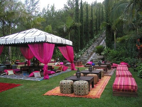Drape fabric or inexpensive curtains (IKEA is great!) from the poles of a tent to create an exotic feel. Extra points for the use of pouffs, outdoor rugs and stools to keep it casual and fun.