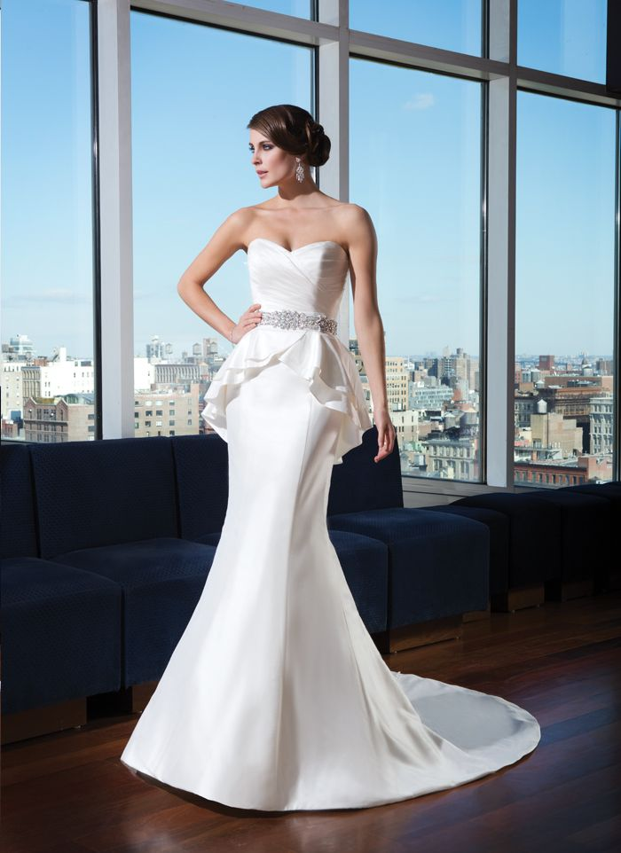 Justin Alexander signature wedding dresses style 9739 Silk dupion mermaid gown features an asymmetrical pleated bodice and a  detachable peplum skirt with a beaded bias belt. Fabric buttons cover  the back zipper and trail onto the hem of the chapel length train.