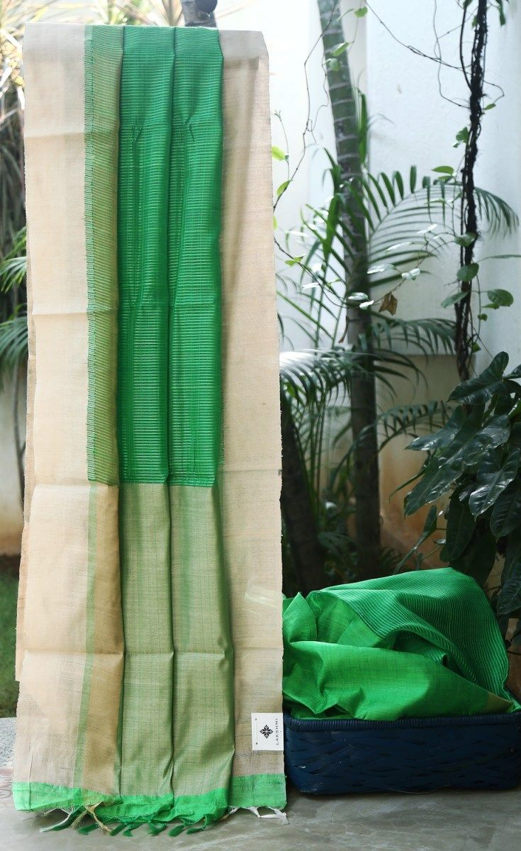 Green textured south silk kora. The piece is offset by a woven white and gold border and pallu