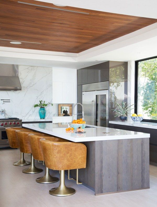 In the kitchen, Blackband Design created the custom swivel barstools at the island | archdigest.com