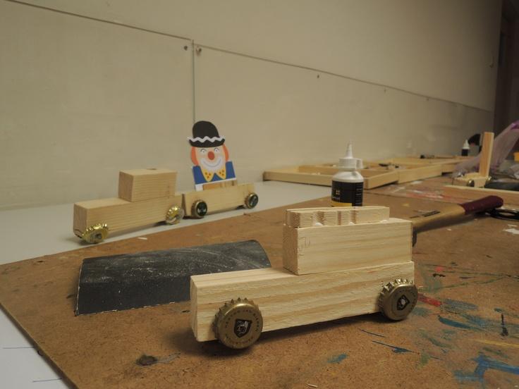 Een carnavalswagen van hout, bierdopjes, houtlijm, spijkertjes en twee vastgeplakte wasknijperhelften om een getekend/gekopieerd plaatje tussen te klemmen. Met wat hulp van ouders goed door kleuters te maken.