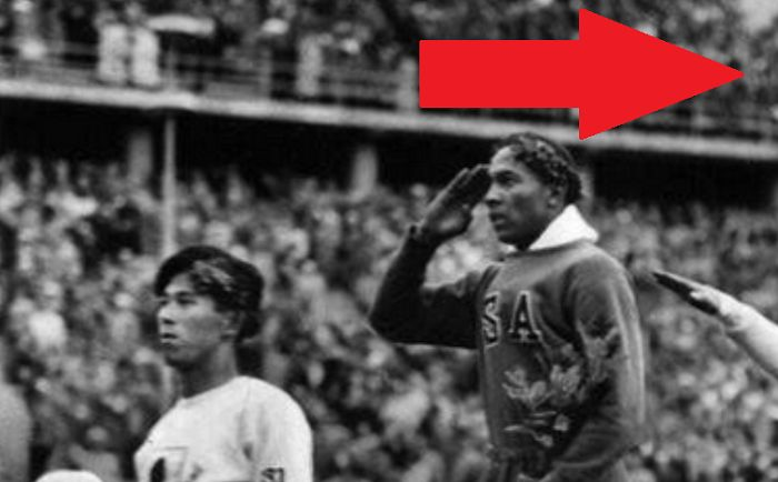 An iconic photo of American track and field legend Jesse Owens saluting the American flag at the 1936 games in Berlin, Germany.