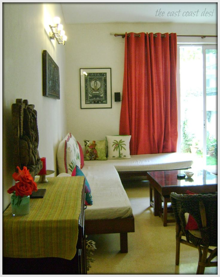 Thangka painting and wooden carvings (from Kerala ) add the art factor to the space. Instead of going the regular sofa set way, the   home owner retained the antique day beds and spruced them up with bright cushions.  Day beds are covered in white sheets which can be easily removed and machine washed, hence are low maintenance. Also the diwan style seating is instantly converted to comfortable guest beds.