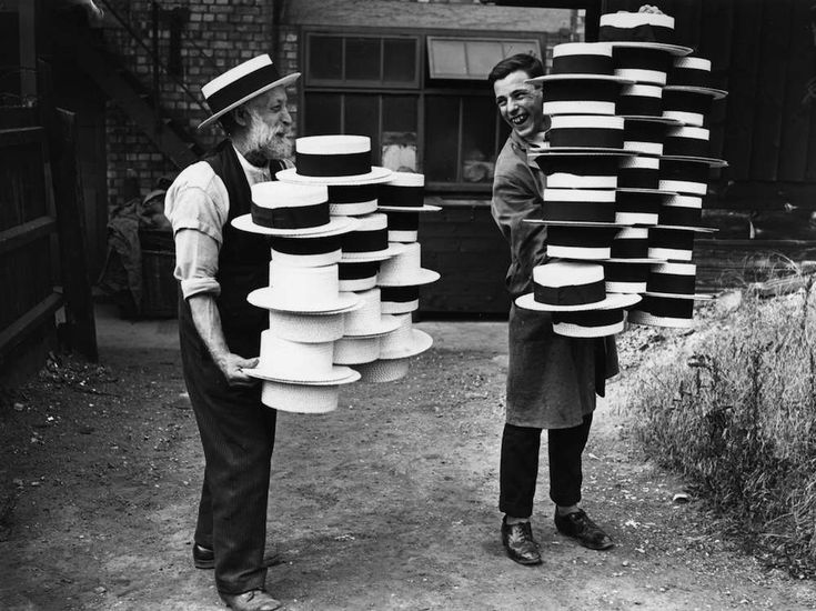 circa 1928: Workers at a hat manufacturers in Luton carrying piles of men's straw hats, which were in demand due to a British heatwave. (Photo by Topical Press Agency/Getty Images)