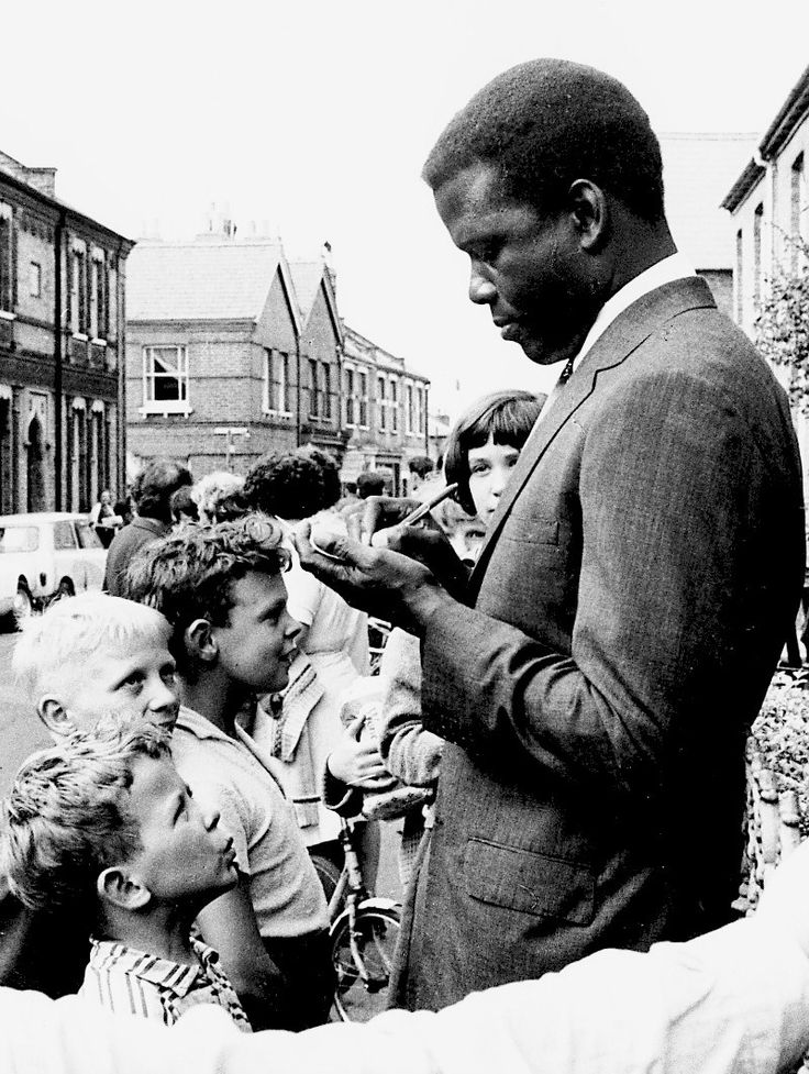 Sidney Poitier signs autographs for some little fans, c. 1960s.