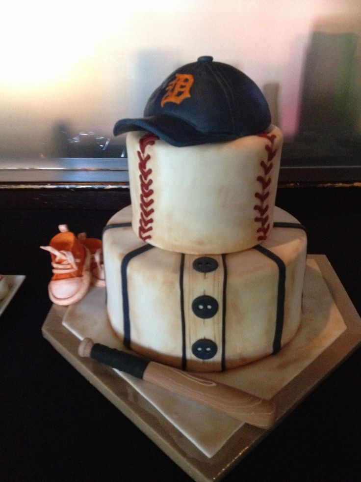 Baseball themed shower cake - Baseball themed cake for my daughter's baby shower.  My first time covering a cake completely with fondant.  It was so much fun.  Fondant shoes and BB bat.   Thanks everyone for the inspiration especially to the original creator!