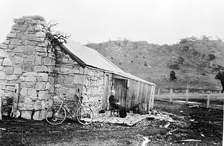 A stone house built circa 1870. A woman sits in front of the house and there is a bicycle leaning against a wall. There appear to be branches growing from the upper part of the chimney. Near Stawell in 1922.