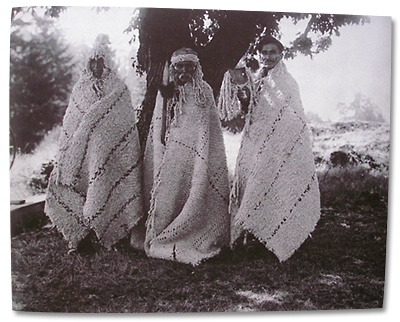 Tommy Paul, David Latasse and Edward Jim, three Saanich chiefs from Tsartlip, wearing twill-weave mountain goat hair blankets and headdresses. The photo was taken in Brentwood Bay in the early 1900s.