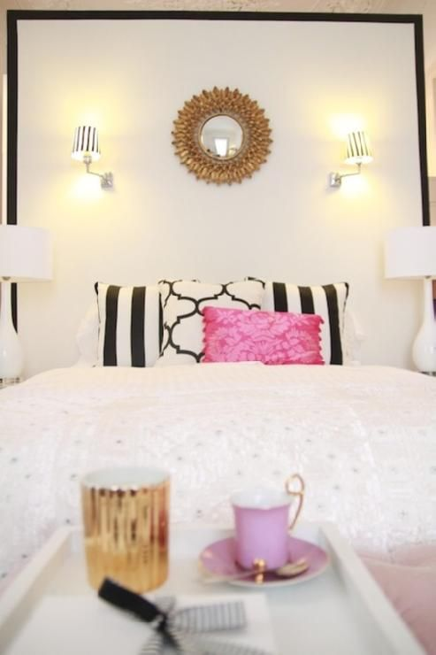 bedrooms - Windsor Smith Riad Jet gold sunburst mirror painted black border accent wall black white pillows hot pink damask pillow glossy white lamps lilac tea cup saucer