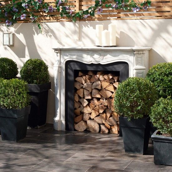 An unused fireplace brings instant glamour to a garden room, whilst providing the perfect place for storing wooden logs too!