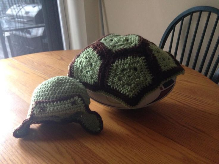 Crocheted turtle shell blanket with a aviator hat.