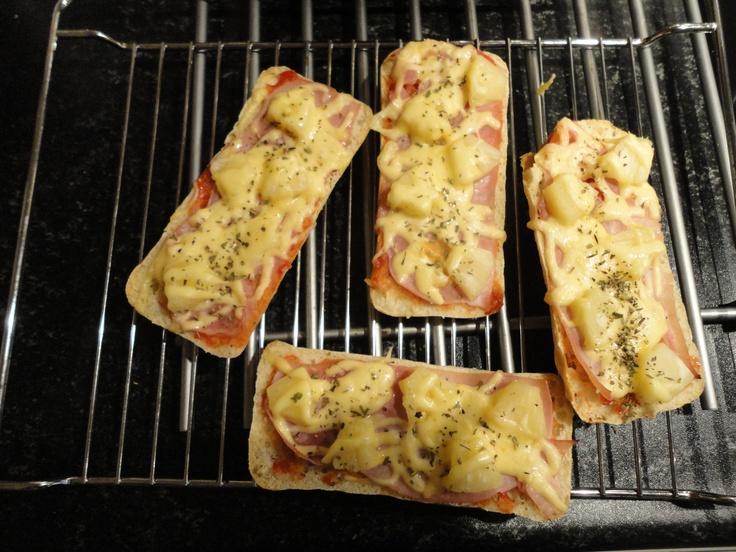 Pizzabroodjes van halve ciabatta´s.   Beleg met tomatenketchup, ham, ananas, kaas en Italiaanse kruiden.