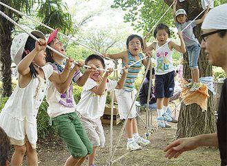 木に括りつけたロープの橋で遊ぶ子どもたち
