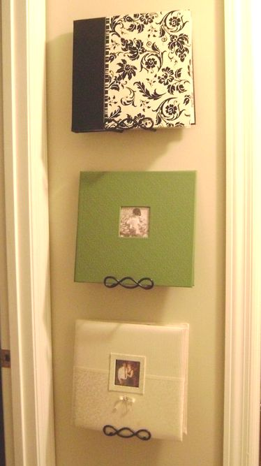 Use plate hangers to display photo albums on the wall so your friends and family, can enjoy them more often. | DIY Home Design Pins.