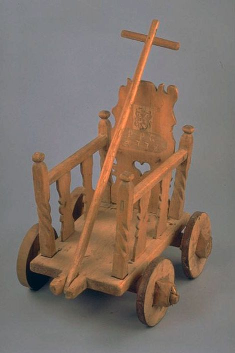1778 Children's pull wagon with a family crest and initials PPG carved on the back of the chair.  Materials: Birchwood and spruce