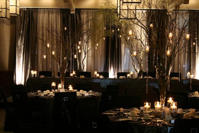 Branch Centerpiece with Candles and Crystal Accents over Black Tablecloth – shared by Wedding Design Studio