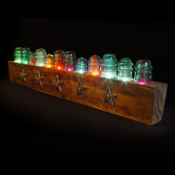 """""""Whistler""""   Originally designed for a fireplace mantle, this ongoing series is assembled from an array of glass insulators set into a wooden block. It is intended to be playful and interactive, inviting owners to switch caps around and change bulb colors to suit their mood. (w:40"""" h:10"""" d:4.5"""")    $675.00"""