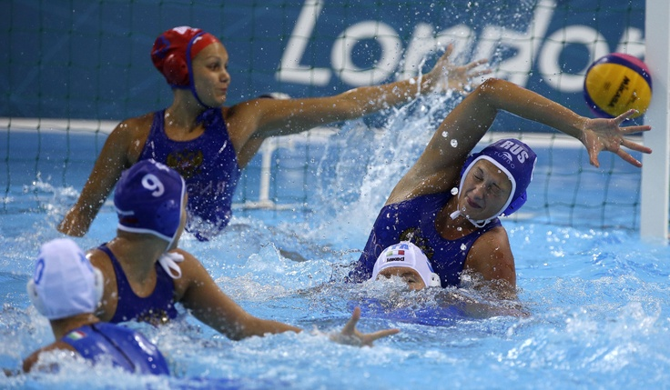 Evgeniia Khokhriakova of Russia is unable to block a shot by Giulia Rambaldi, bottom left, of Italy during a preliminary women's water polo match at the 2012 Summer Olympics, Wednesday, Aug. 1, 2012, in London.