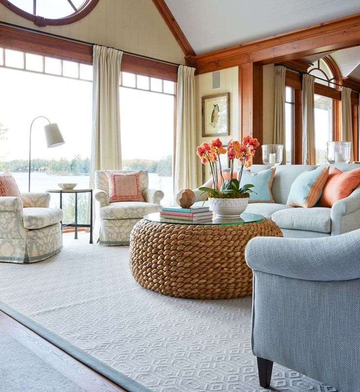"""A pair of Bill Blass sofas in pale robin's-egg blue """"sets the landscape for the living room,"""" says Hepfer. Two custom swivel club chairs by Hepfer make turning toward the view easy. Desert Modern woven cocktail table, Ralph Lauren Home. Soft Landing.  Home Tour: A Lake House by Anne Hepfer 