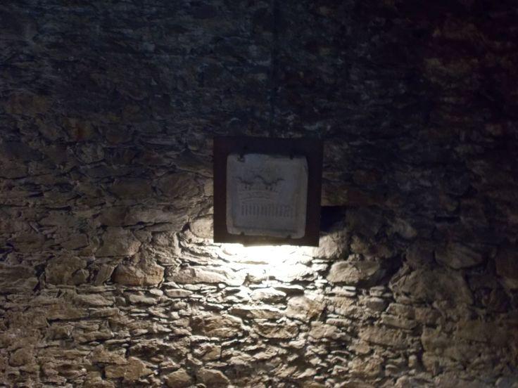 Humilitas (Borromeo) - Palazzo Borromeo, Isola Bella, Lago Maggiore (VB). Frammento di materiale lapideo del XV-XVI secolo, proveniente da un'antica casa Borromeo di Milano, collocato alla parete della scala ellittica in pietra costruita nel 1689, che collega le grotte al primo piano nobile e ai piani superiori.