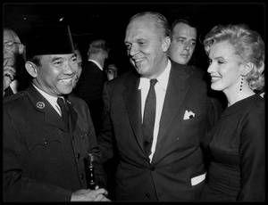 """1er Juin 1956 /  Le président indonésien SOEKARNO était à Los Angeles pour y faire la tournée des studios et s'adresser à l'Association """"Motion Picture Producers"""". Joshua LOGAN organisa une soirée au """"Beverly Hills Hotel"""", pour le président indonésien, car c'était son frère, Marshall NOBLE, qui organisait la visite du président à Hollywood. Marilyn se rendit à cette soirée. Les journalistes lui firent la surprise d'un gâteau d'anniversaire juste avant qu'elle ne prenne son avion pour…"""