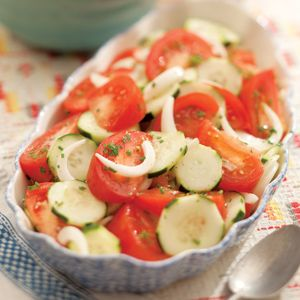 Summer Tomato, Onion & Cucumber Salad  3 tablespoons rice vinegar1 tablespoon canola oil1 teaspoon honey1/2 teaspoon salt1/2 teaspoon freshly ground pepper, or more to taste2 medium cucumbers4 medium tomatoes, cut into 1/2-inch wedges1 Vidalia or other sweet onion, halved and very thinly sliced2 tablespoons coarsely chopped fresh herbs, such as flat-leaf parsley, chives and/or tarragon