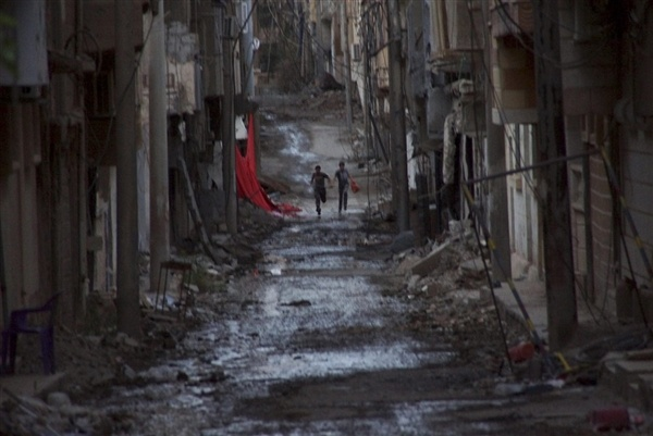 People flee fighting on a Syrian street on May 18. A new UN report cites systematic war crimes.