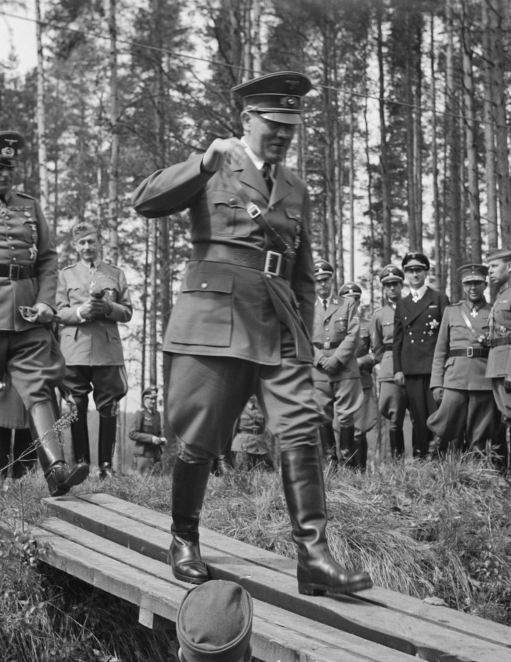 A smiling Adolf Hitler, in Finland on the occasion of Marshal Mannerheim's 75th birthday, gingerly walks the plank followed by Marshal Wilhelm Keitel (June 4, 1942). Mannerheim, in the background between Keitel and Hitler (who was not an admirer) watches with a wry smile. German and Finnish officers are also seen in the background.