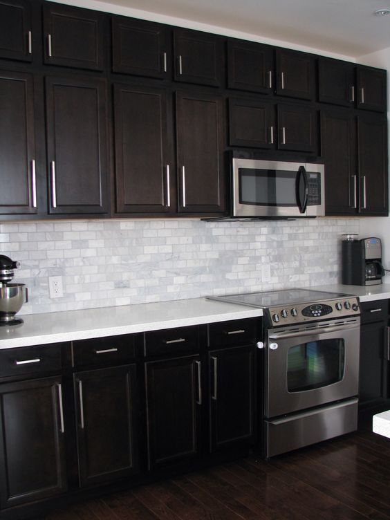 Dark Birch kitchen cabinets with Shining White Quartz counters and White Marble backsplash: