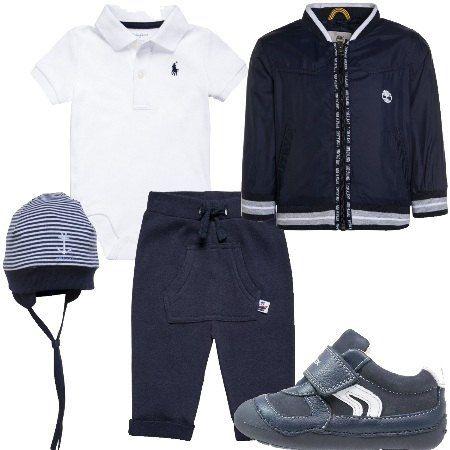 Outfit da neonato composto da polo body a maniche corte, pantalone sportivo e giacchetto mezza stagione con chiusura a zip. Le scarpe sono delle sneakers basse con strappo. Cappellino a righe.