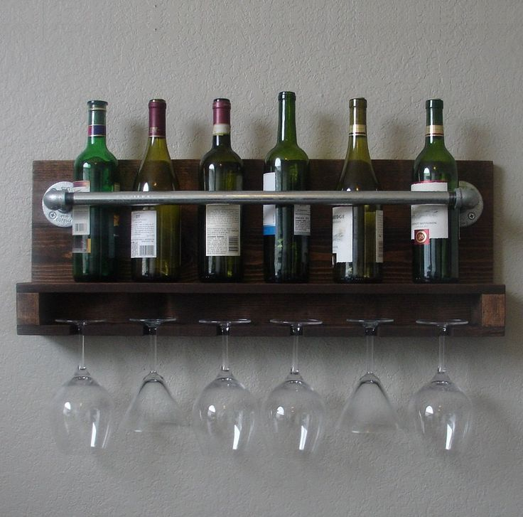 Industrial rustic meets modern in this handcrafted wine rack. Perfect for any home, apartment, or condo.  Made from solid wood. It has been sanded down, then stained and sealed with a beautiful dark walnut finish.  This piece does not include the accessory items as shown in the pictures.  The color of the stained wood captured in the photos might vary slightly.  Item Dimensions: 29 in wide x 11.25 in tall x 4.75 in deep  Keyhole hangers are installed on the back with heavy duty mounting…