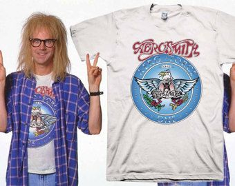 Garth Aerosmith Halloween Costume T-shirt as seen in the Waynes World movie. Printed on 100% combed ringspun cotton T-shirt, which dont shrink much. Please NOTE: Slim Fit T-shirts run small. Check the size chart prior to your purchase.  Made to order. Ships in 1-2 business days. Should you have any questions please let us know via Etsy Convo. Thank you