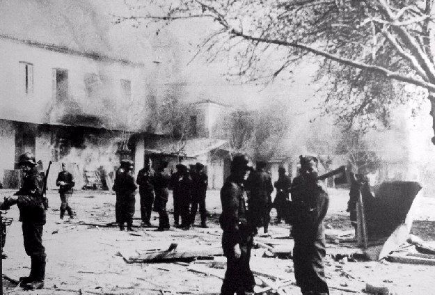 June 10, 1944 - German troops in front of buildings set ablaze in Distomo, during the massacre. The Distomo massacre was a Nazi war crime perpetrated by members of the Waffen-SS in the village of Distomo, Greece, during the Axis occupation of Greece during World War II.