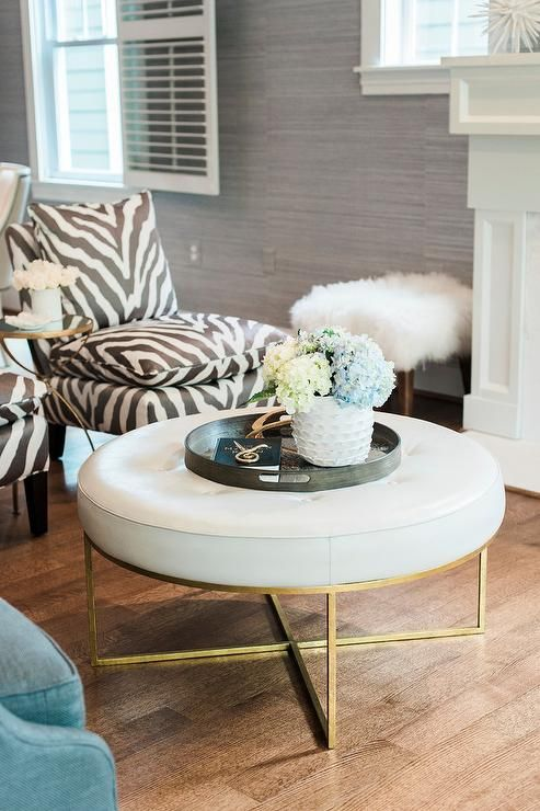 Contemporary Living Room Boasts A Round White Leather Tufted Ottoman Seating Two Black And Zebra Chairs Flanking Gl Top Br Accent Tab