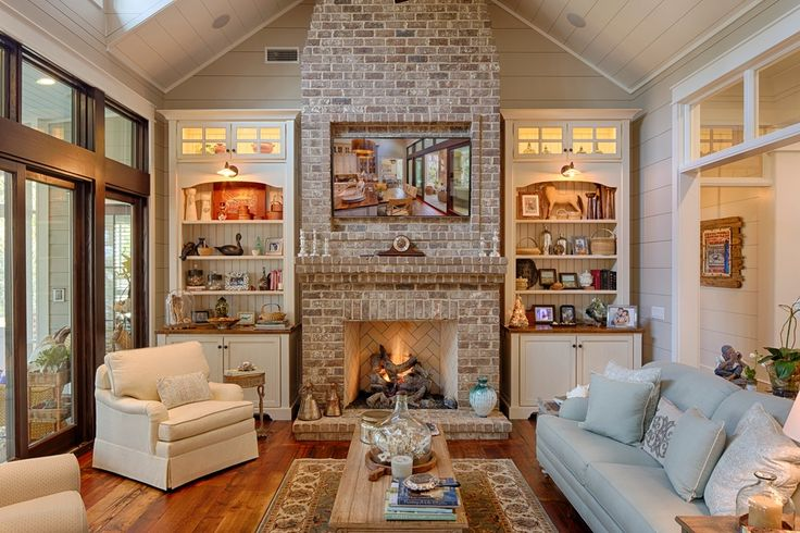 Country Living Room with Wall sconce, stone fireplace, Crown molding, Built-in bookshelf, Manchester Blend Bricks, Carpet