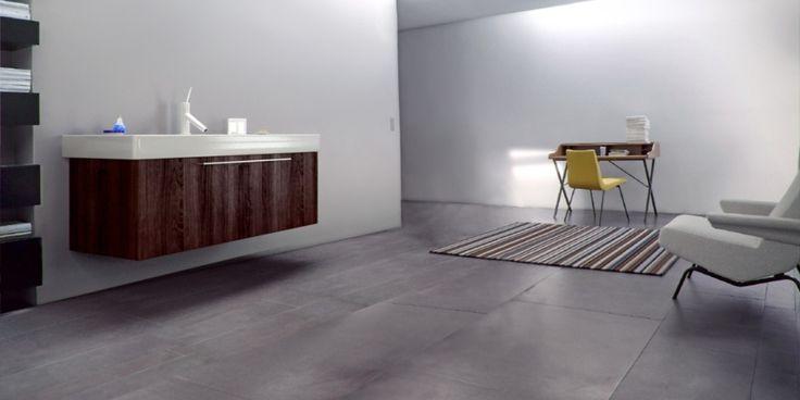 Badrum med snygga moderna badrumsmöbler och golv av klinker som ser ut som betong ur serien på Stan Malmö