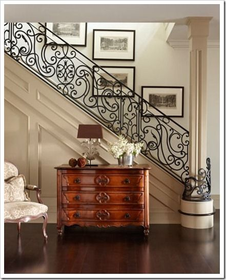 The iron scroll work wrapping around the front pillar makes the staircase extra special.