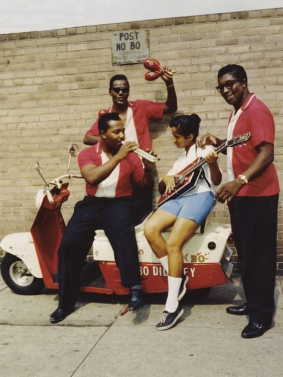 Jerome Green, Clifton James seated with young fan holding guitar and Bo Diddley, in New York City, 1959