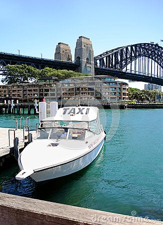 A taxi docked in Sidney harbour with Sidney bridge ad apartments in the background.