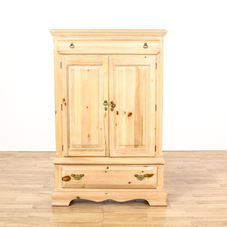 This country chic armoire is featured in a solid wood with a raw light pine finish. This rustic wardrobe dresser has 3 spacious drawers, 2 carved panel doors and a large interior cabinet with shelving. Perfect for storing shoes and coats in an entryway! #americantraditional #dressers #armoireorwardrobe #sandiegovintage #vintagefurniture