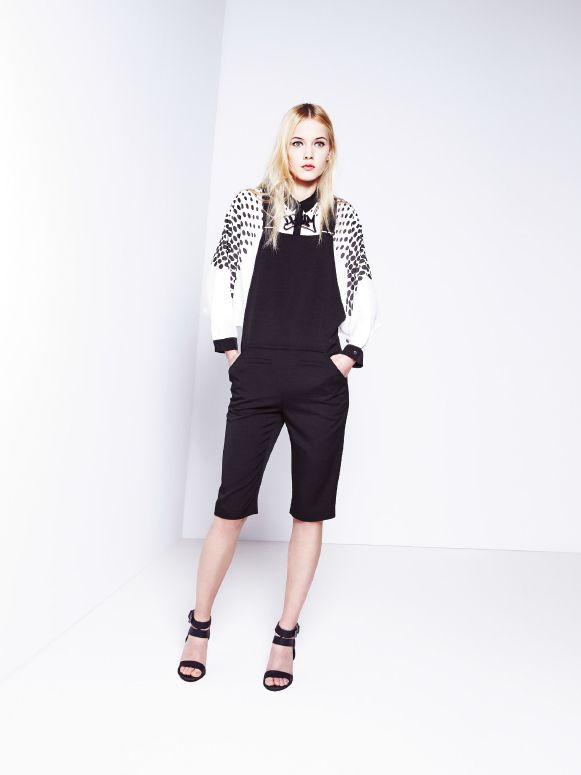 Czarny kombinezon i biała, oversizowa koszula z motywem w groszki.