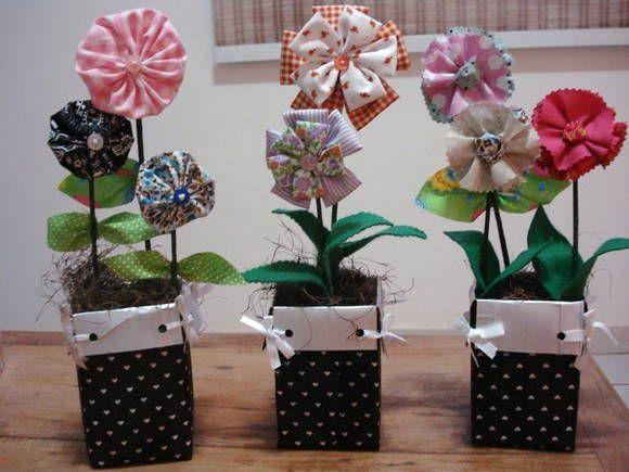 Vasinho com caixa de leite envolvida em tecido e 3 flores em fuxico.  Temos diversos tipos de flores e vasos.  Pedido minimo 10 unidades R$ 12,00