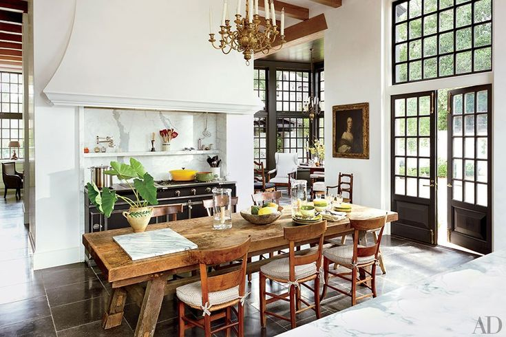 In a Baton Rouge kitchen, a 17th-century portrait overlooks the kitchen table, which is surrounded with antique French chairs.