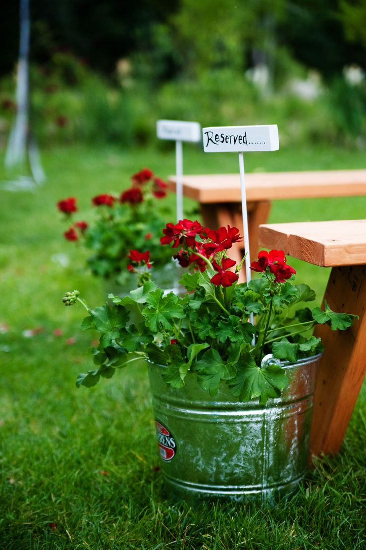 Wedding seating arrangement idea -- place reserved signs into flower pots to save seats at the ceremony for your family!