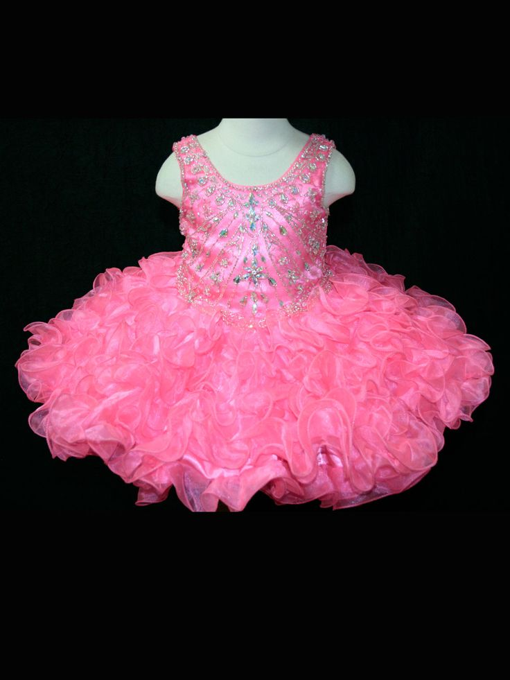 A glitzy and girlie baby pageant dress by Little Rosie BR1062. This sweet pageant dress features a beaded scoop halter neckline that tops off a heavily embellished bodice with slightly dropped waisstline. The full organza skirt ruffles magically with the touch of a sweet princess. A lace up back seals up this design. Available in Fuchsia and Coral. Make sure your girl looks her best wearing our exclusive pageant accessories.
