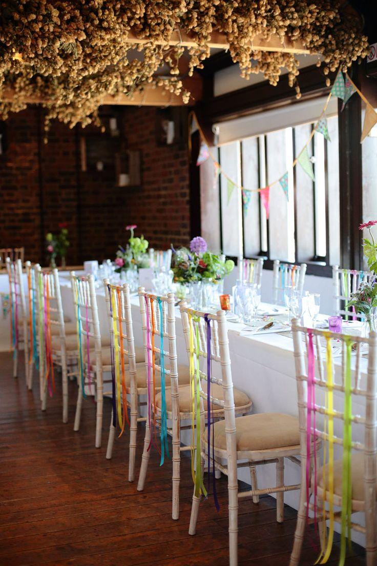 Different coloured ribbon hanging from the reception venue chairs - Dasha Caffrey - A colourful village hall wedding in Kent with lots of DIY and a tea length wedding gown. Photography by Dasha Caffrey.